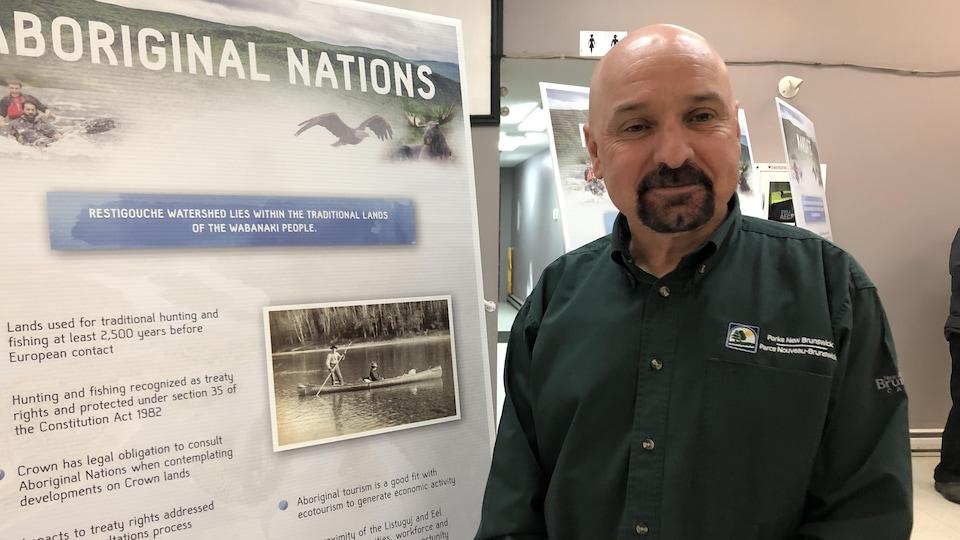 Allen Bard est photographié devant un panneau d'information.