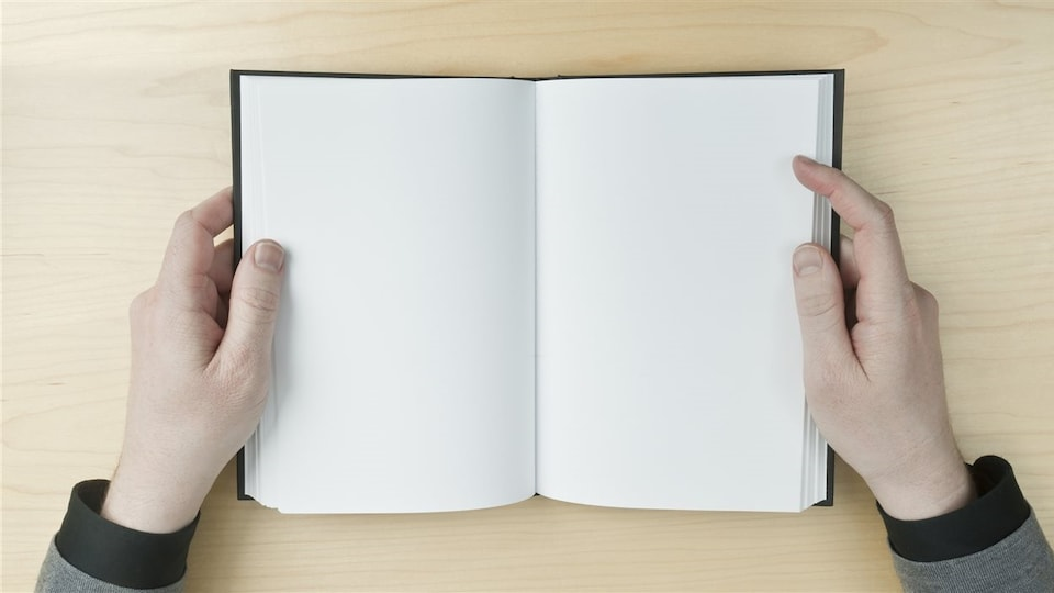 Une personne tient un livre ouvert qui n'a que des pages blanches.