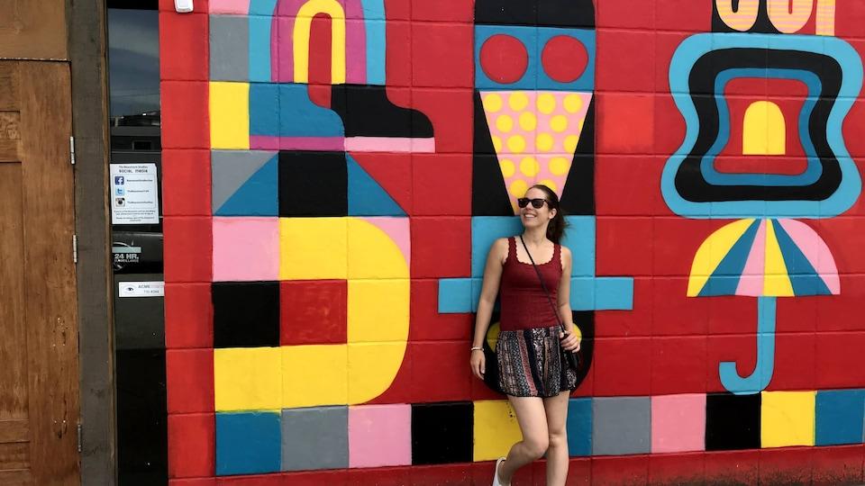Anaïs Collin pose devant une murale colorée à Vancouver.