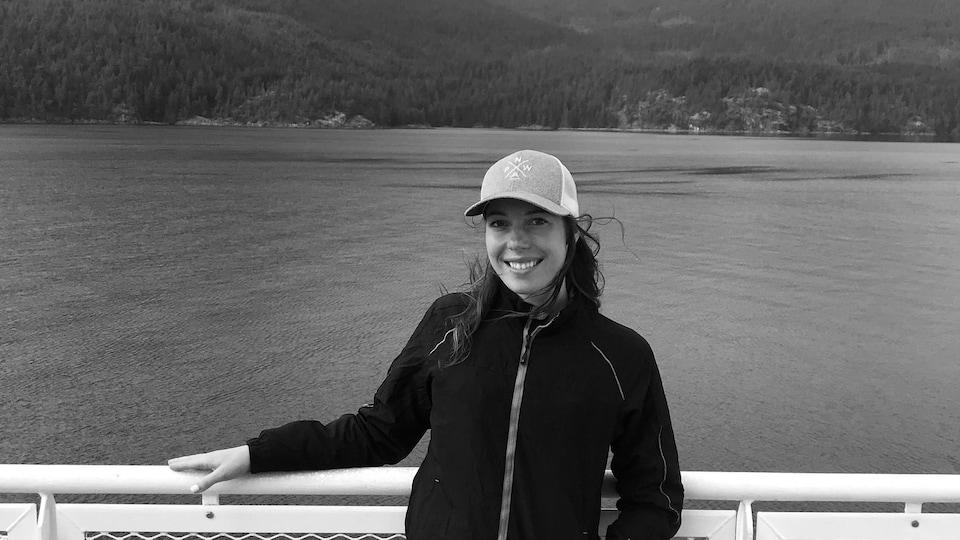 Anaïs Collin sourit  sur un traversier de BC Ferries avec les montagnes en arrière-plan.