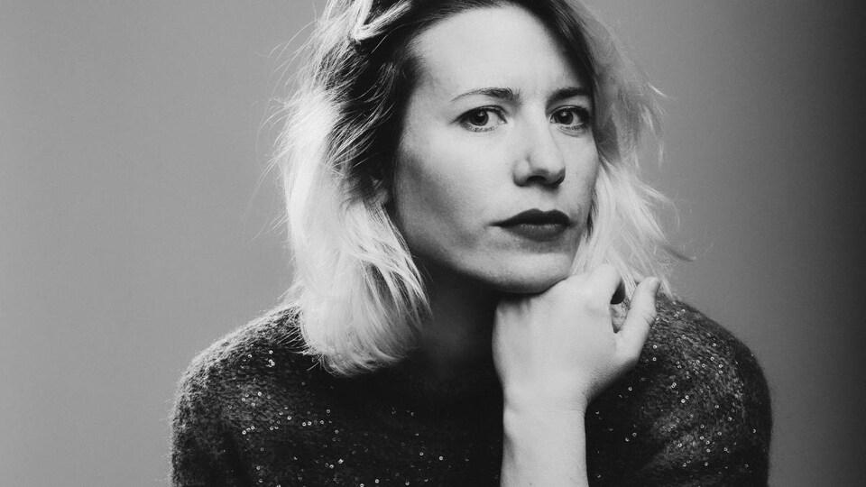 Andréa Saunier pose sur un fond noir et blanc.