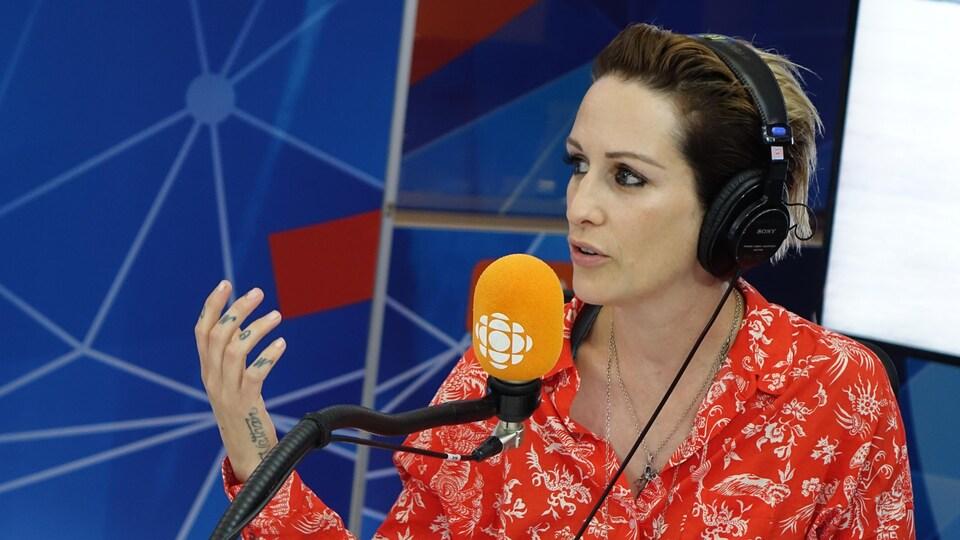Une femme parle avec expression devant un micro orange dans un studio de radio.