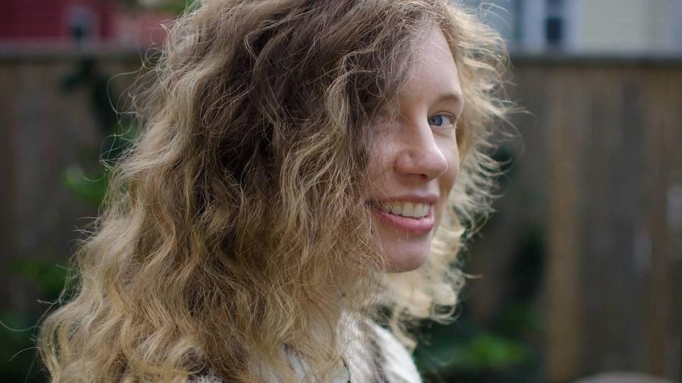 Ann Helga regarde la caméra en souriant, le regard de côté, et porte un pull islandais.