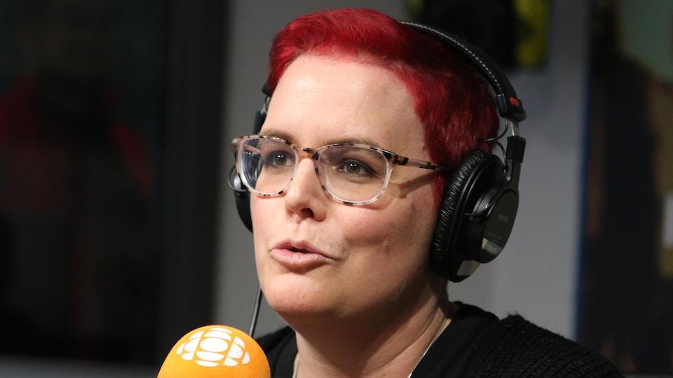 Une femme aux cheveux rouges et aux lunettes de vue à cadre moucheté parle au micro.