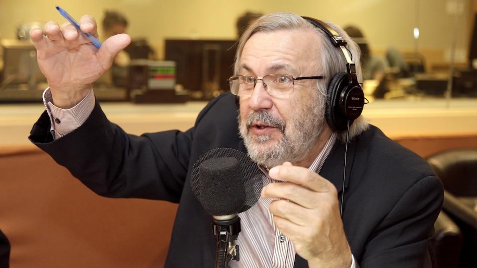 Yanick Villedieu parle dans un micro de radio en levant les bras dans les airs.