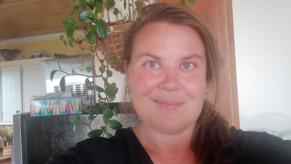 Une femme aux yeux bleus et cheveux longs châtains sourit à la caméra..