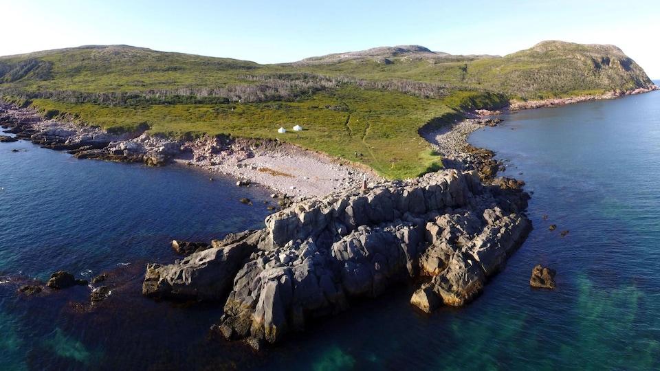 Vue aérienne d'une pointe d'île aux rives érodées, en plein soleil.