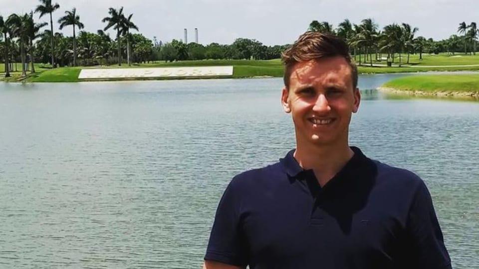 Anthony Demers, nouveau professionel au Club de golf Ste-Marguerite de Sept-Îles, devant un étendu d'eau avec un terrain de golf et des palmiers derrière lui.