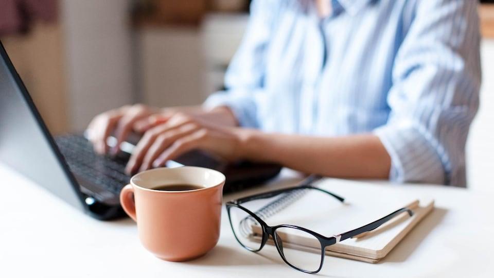 Une femme travaille sur un ordinateur portable. Une tasse de café et des lunettes se trouvent en avant-plan.
