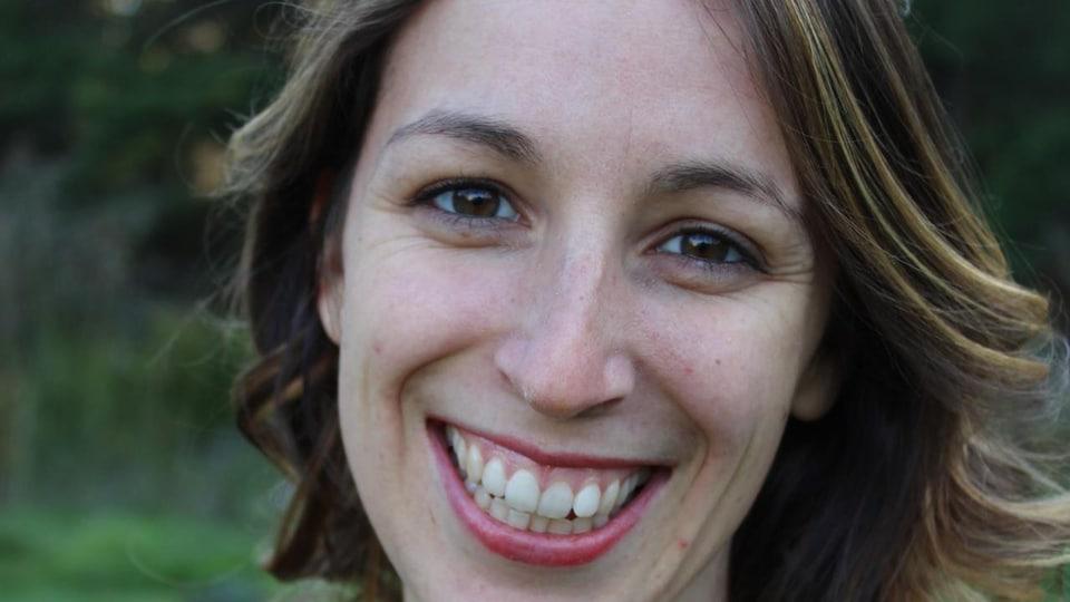 Une femme avec des cheveux  jusqu'aux épaules sourie.