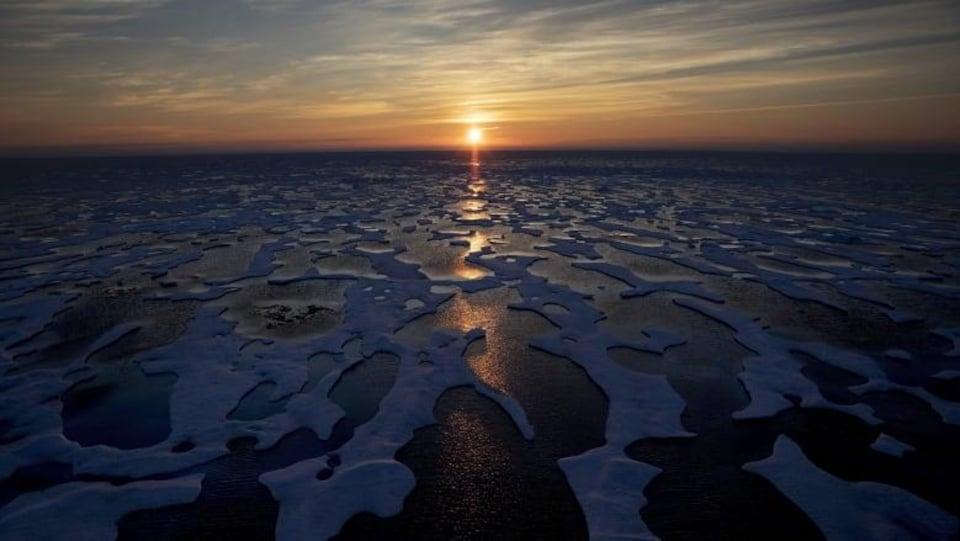 Des morceaux de glace flottent sur l'eau au soleil couchant.