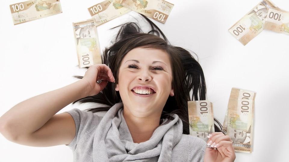 Une jeune femme est couchée et est entourée de billets de 100 $.