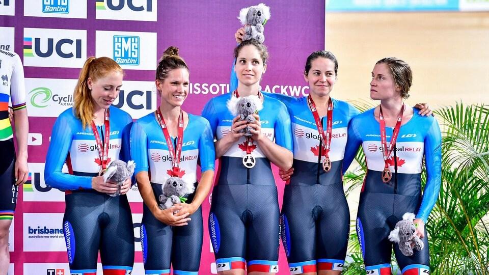 Cinq cyclistes avec une médaille de bronze sur un podium