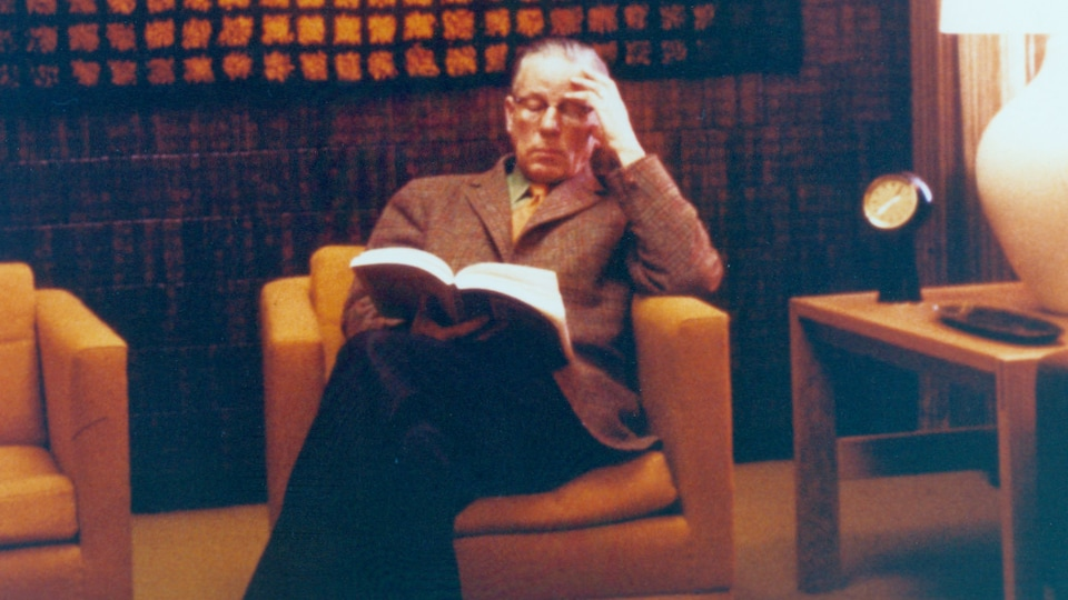 Armand Frappier lit un livre sur une chaise