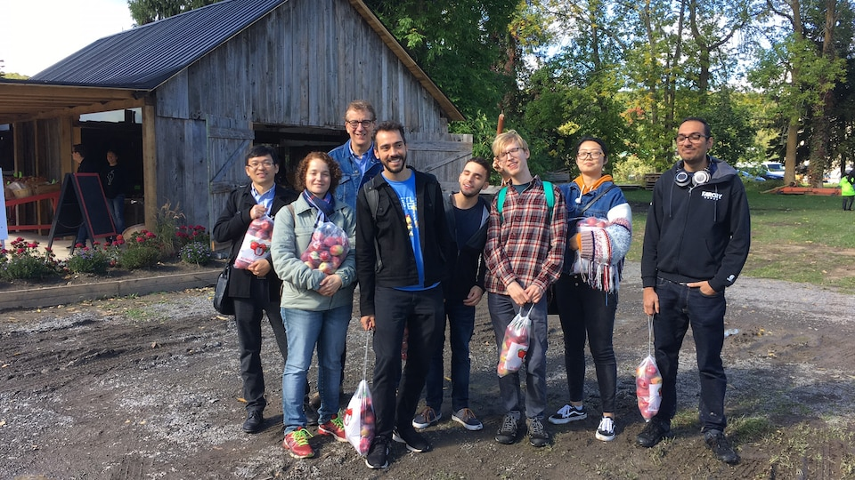 Une groupe d'immigrants tenant des sacs de pommes.