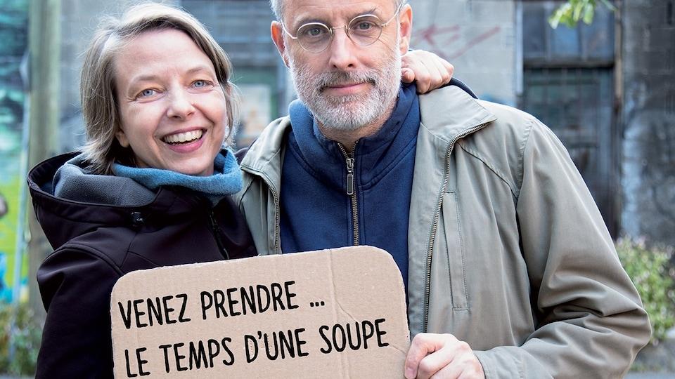 Annie Roy et Pierre Allard tiennent une affiche