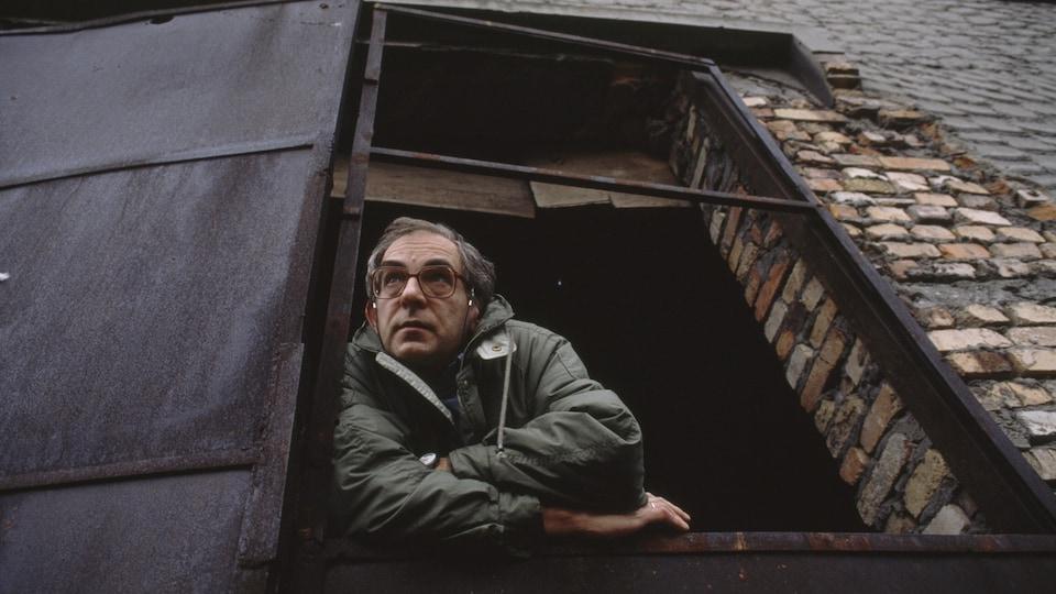 Le cinéaste Krzysztof Kieslowski en 1990 pose sur le rebord d'une fenêtre.