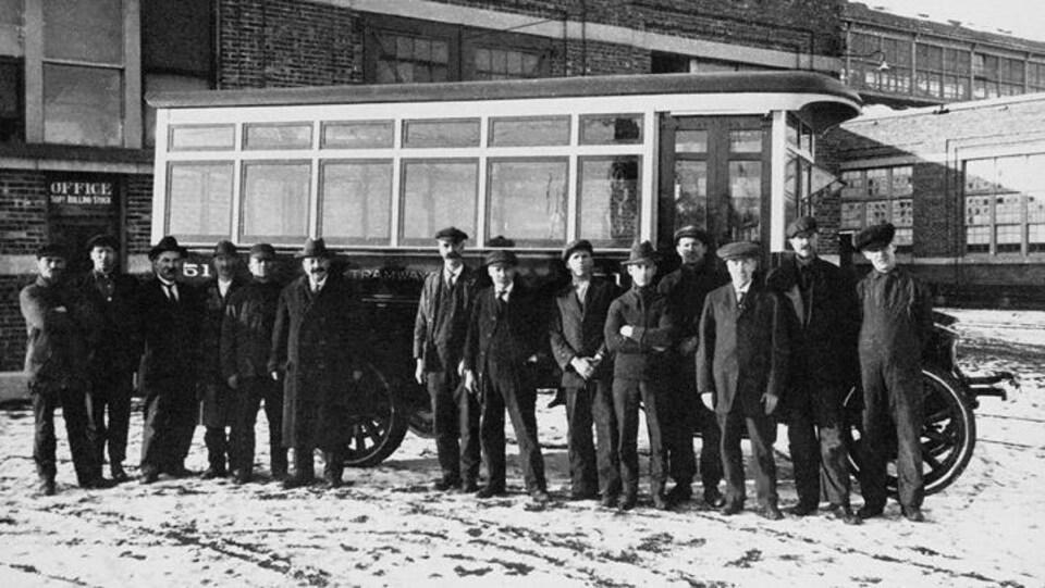 Une photo en noir et blanc montrant plusieurs hommes devant un autobus.