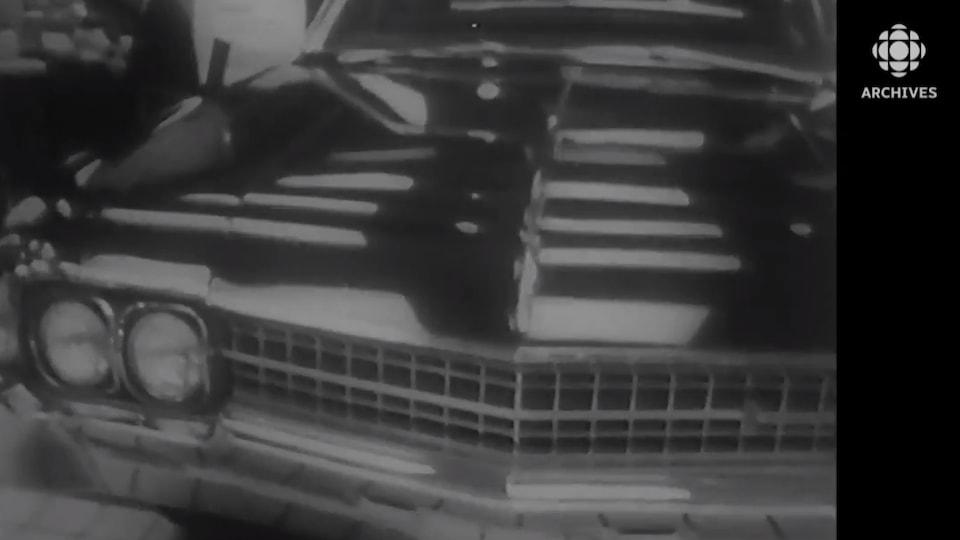 Vue partielle d'une voiture noire dans les années 1960.