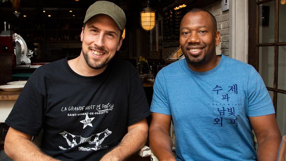 Les deux hommes sont photographiés souriants et assis à une table de restaurant.