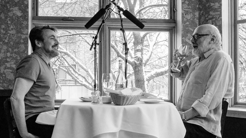 Les deux hommes sont vus en train de manger à une table, près d'une fenêtre.