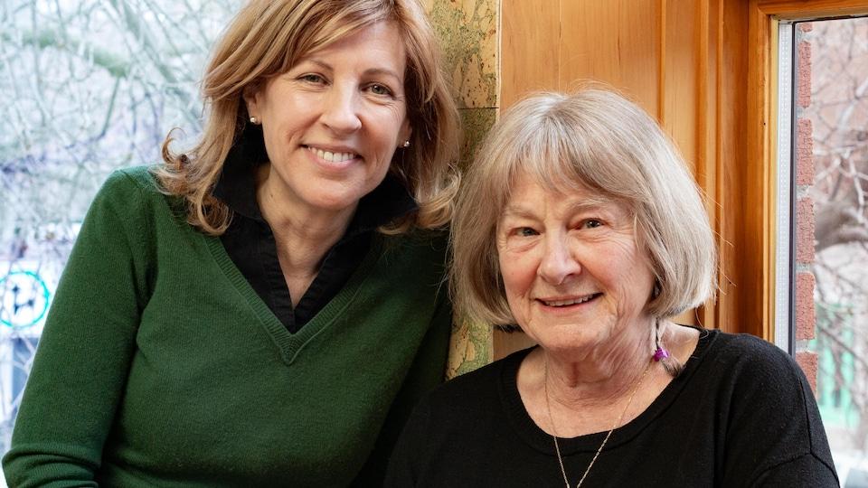 Les deux femmes posent et sourient devant une fenêtre de restaurant.