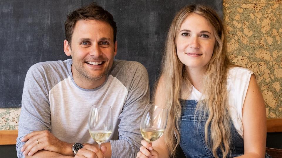 Les deux invités posent à la table avec un verre de vin à la main.