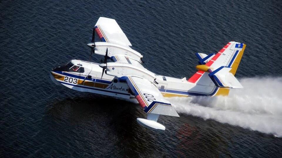 Un avion citerne vole au-dessus d'un lac.