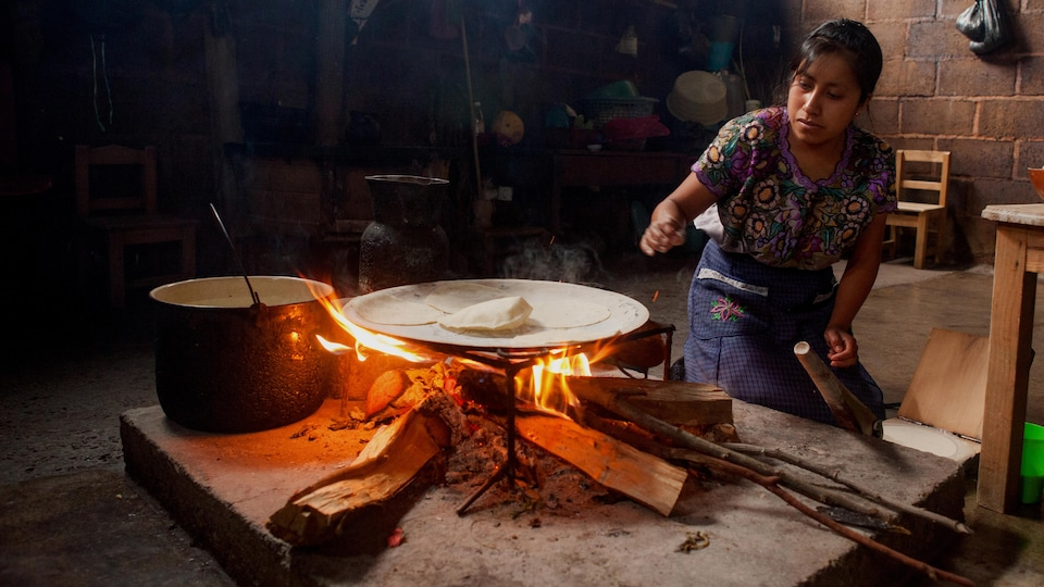 Une femme à genou près d'un feu de bois sur lequel reposent une plaque et une pâte.