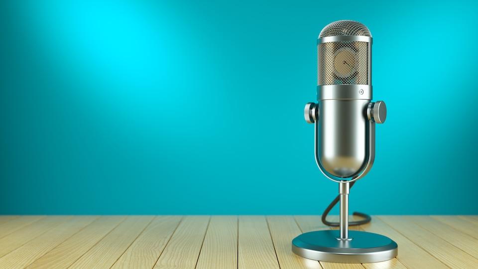 Un micro de radio posé sur un plancher devant un fond uni
