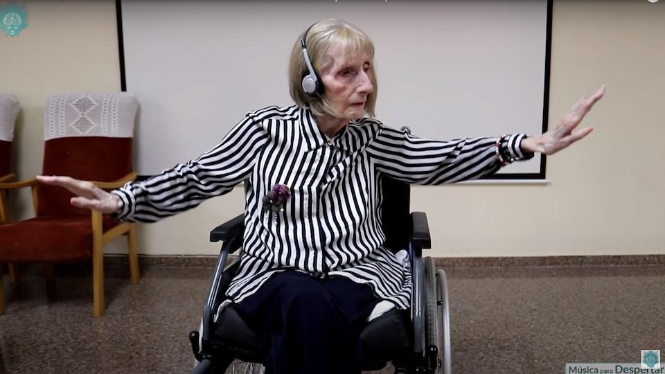 Une femme âgée assise dans un fauteuil roulant, les bras étendus dans les airs avec grâce.