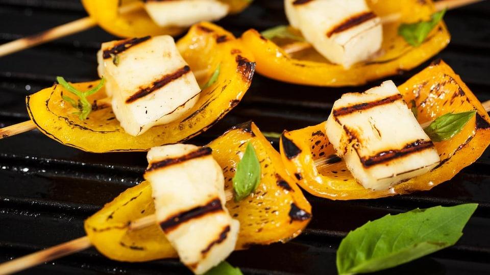 Photo de brochettes de poivrons et de halloumi qui cuisent sur un barbecue.