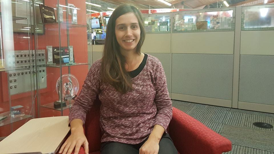 Une photo de Noémie Bencteux du Conseil jeunesse francophone de la C.-B. assise dans la salle des nouvelles de Radio-Canada à Vancouver