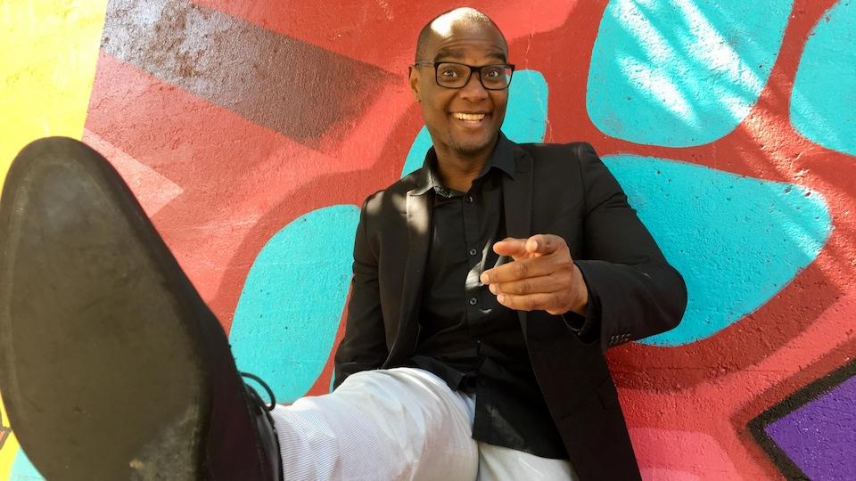 Un homme adossé à un mur coloré a la jambe levé et pointe la caméra du doigt le sourire aux lèvres.