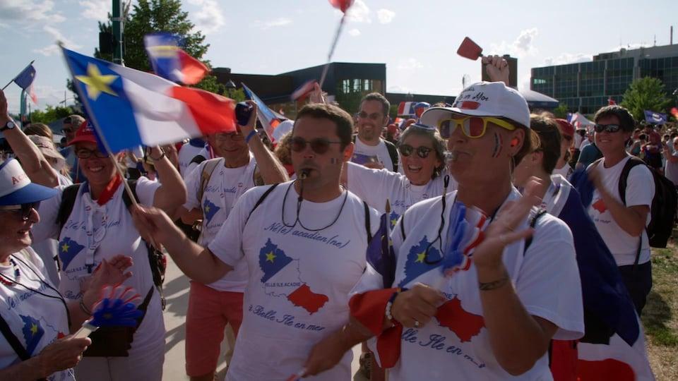 Des Bellilois, sifflets à la bouche, portant des chandails de l'Acadie et arborant des drapeaux de l'Acadie.