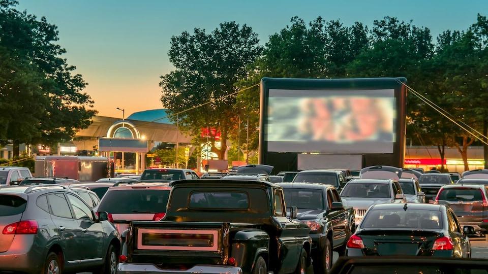 Des voitures stationnées devant un écran de cinéma en plein air.