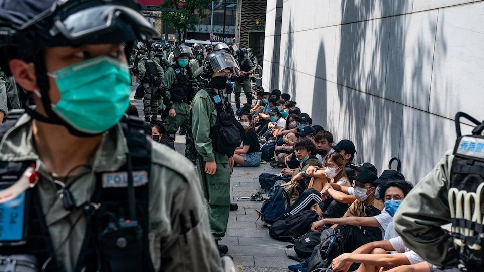 Des dizaines de personnes assises par terre sont surveillées par des policiers casqués et masqué