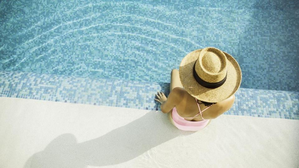 Vue aérienne d'une femme portant un chapeau de paille assise sur le rebord d'une piscine.