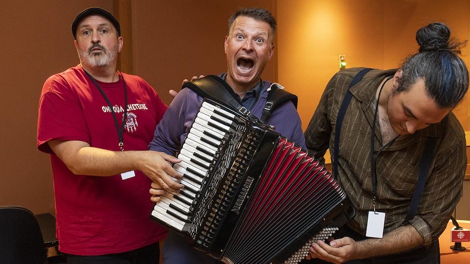 Steve Normandin, Stéphan Bureau et Antoine Pigeon-Bourque manipulent un accordéon à la blague.