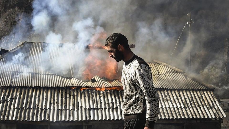 Un homme passe devant une maison en feu.