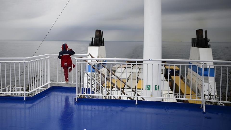 Vu de dos, un enfant se trouve sur le pont supérieur d'un cargo et regarde la mer.