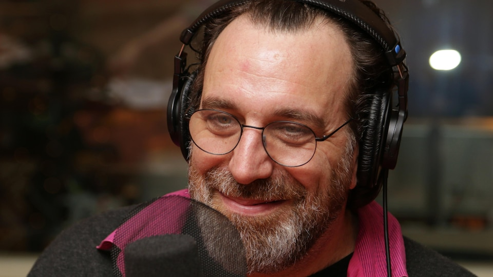 Chilly Gonzales sourit devant un micro de radio.