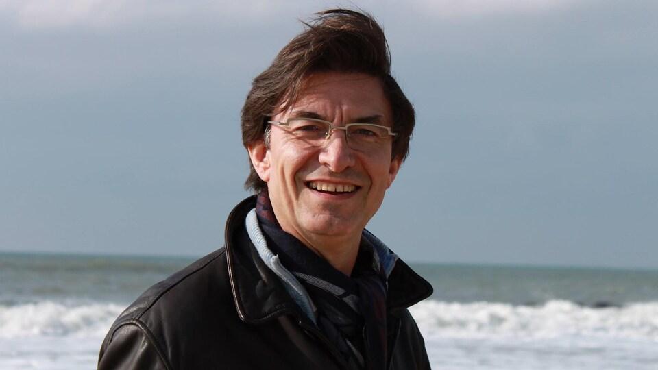 Christian Buchet sourit et pose devant la mer.