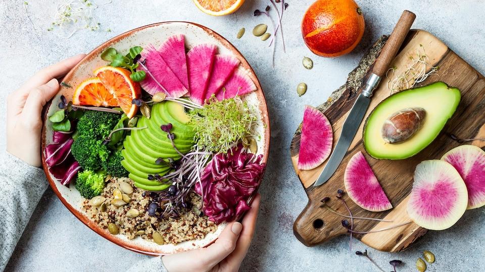 Mains d'une femme tenant un bol du Bouddha au quinoa, à l'avocat, aux pousses, à l'orange, au brocoli, au radis et aux pousses.