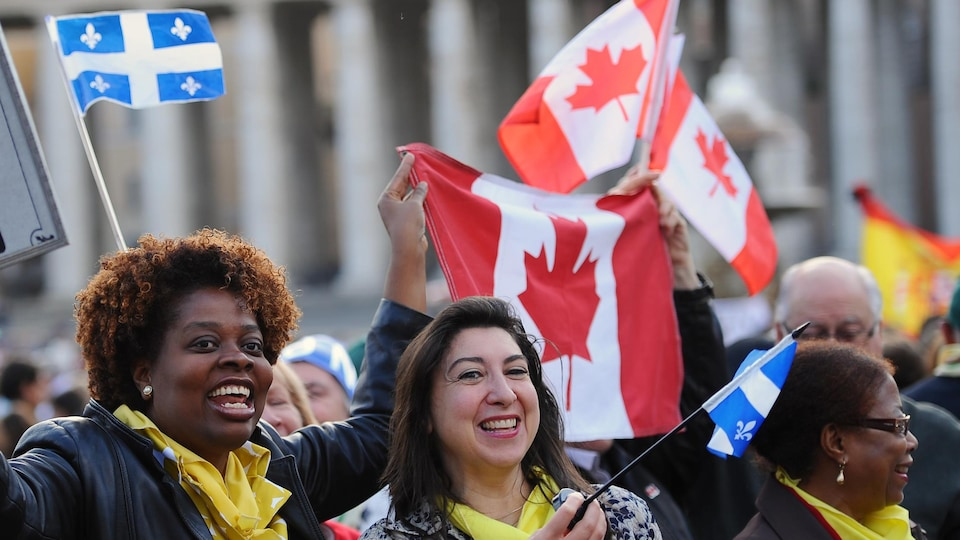 Des gens brandissent des drapeaux québécois et canadiens dans une foule.