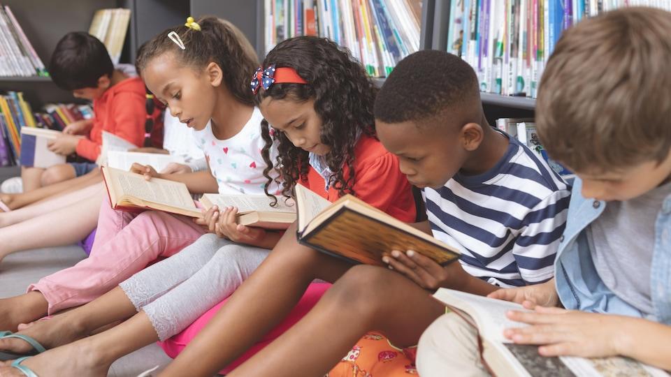 Des enfants assis devant une étagère lisent des livres.