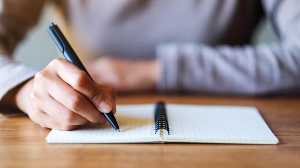 Une femme écrit avec un styl dans un petit carnet à spirales.