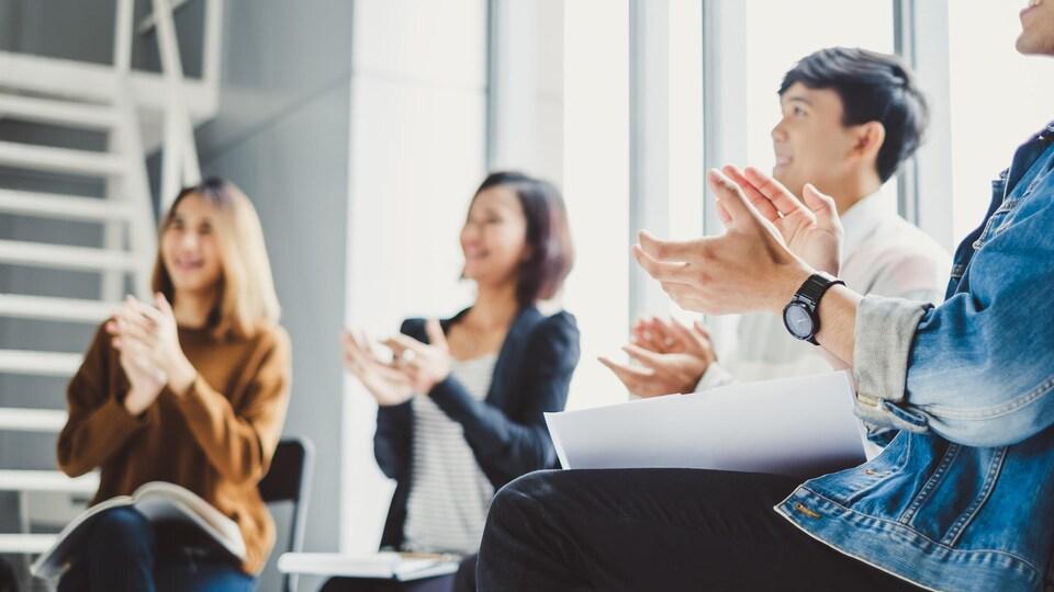 De jeunes employés d'entreprise applaudissent en souriant lors d'une réunion.