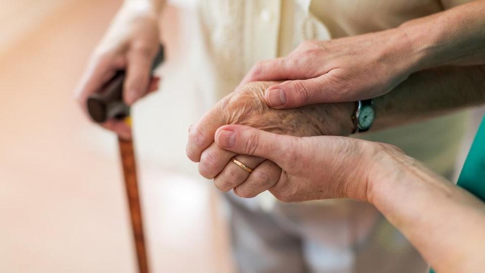 Gros plan sur les mains d'une femme tenant la main d'une personne âgée qui se déplace avec une canne.