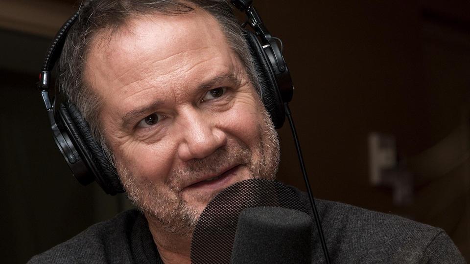 Portrait devant un micro de radio.